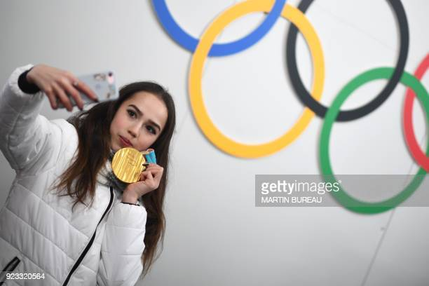 Russia's figure skating gold medallist Alina Zagitova poses for a selfie in front of Olympic rings backstage at the Athletes' Lounge during the medal...