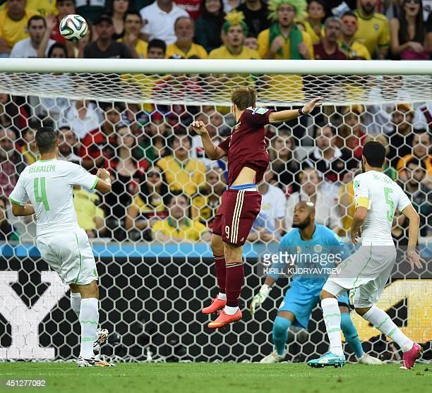Russia's forward Alexander Kokorin scores his team's first goal past Algeria's goalkeeper Rais Mbohli during a Group H football match between Algeria...