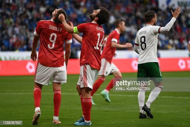 Russia's forward Alexander Sobolev and Russia's defender Georgi Dzhikiya react during the friendly football match Russia v Bulgaria in Moscow on June...