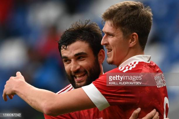 Russia's forward Alexander Sobolev celebrates with Russia's defender Georgi Dzhikiya after scoring the opening goal from the penalty spot during the...