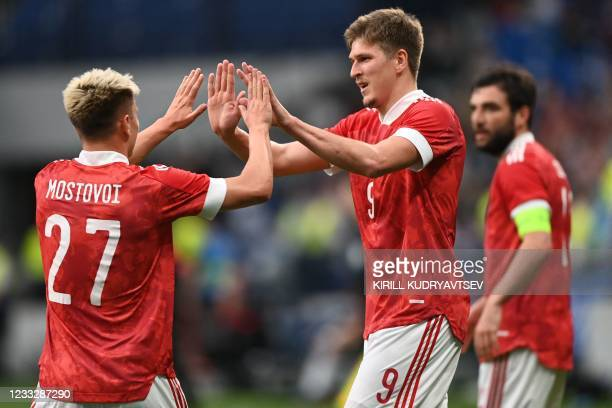 Russia's forward Alexander Sobolev celebrates with Russia's midfielder Andrey Mostovoy after scoring the opening goal from the penalty spot during...