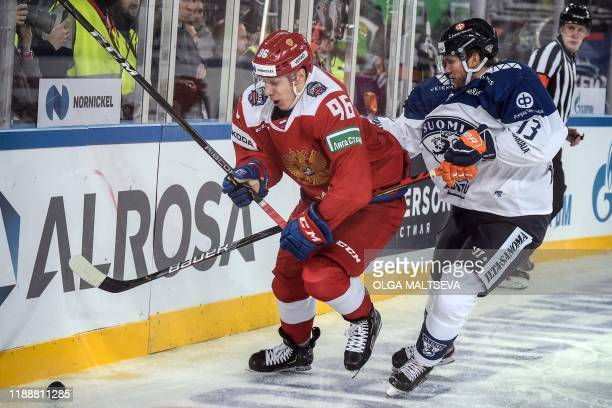 Russia's forward Andrei Kuzmenko vies with Finland's defender Valtteri Kemilainen during the Channel One Cup of the Euro Hockey Tour ice hockey match...