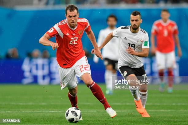Russia's forward Artem Dzyuba and Egypt's midfielder Abdallah Said vie during the Russia 2018 World Cup Group A football match between Russia and...