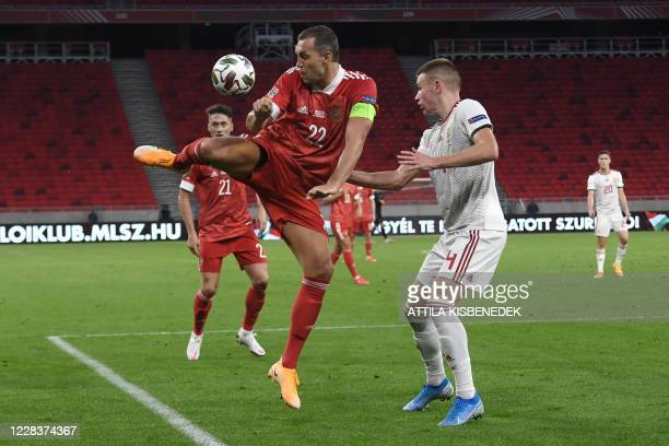 Russia's forward Artem Dzyuba and Hungary's defender Attila Szalai vie for the ball during the UEFA Nations League football match between Hungary and...