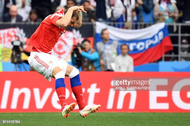 TOPSHOT Russia's forward Artem Dzyuba celebrates after scoring their third goal during the Russia 2018 World Cup Group A football match between...