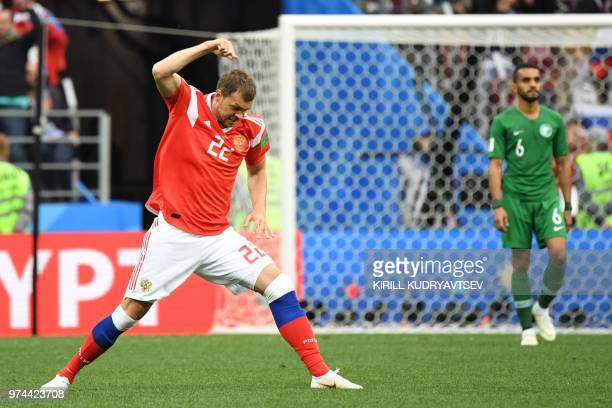 Russia's forward Artem Dzyuba celebrates after scoring their third goal during the Russia 2018 World Cup Group A football match between Russia and...