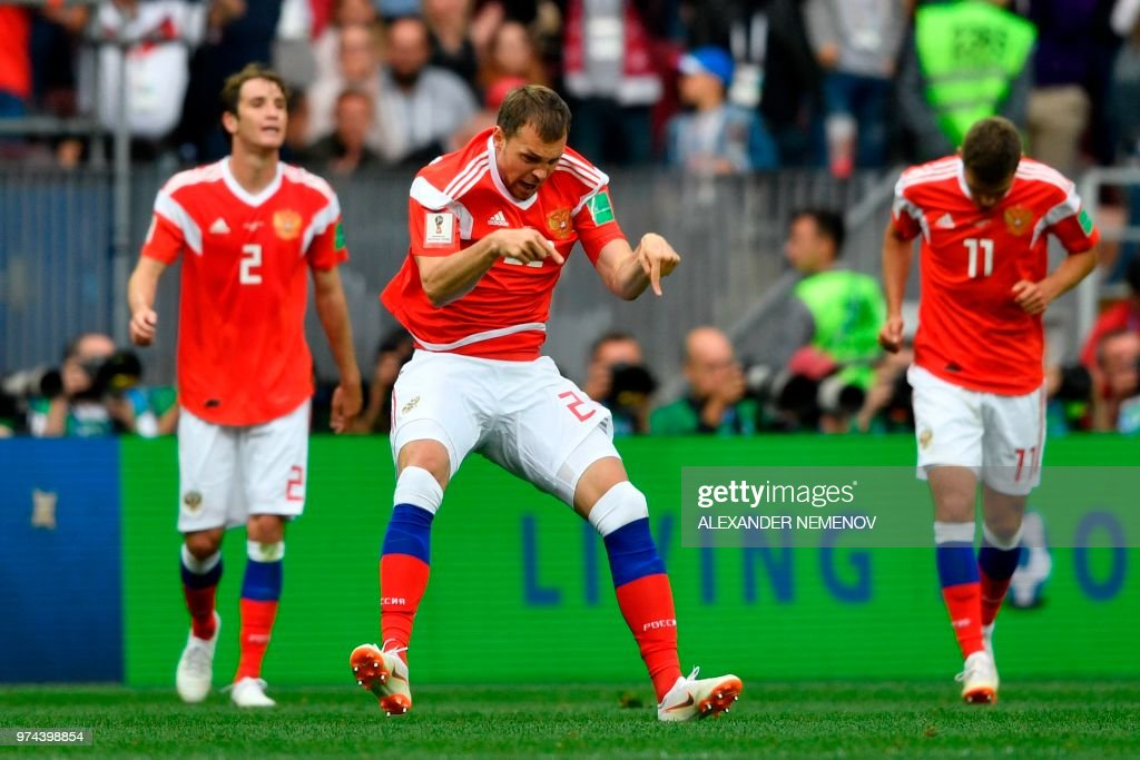 TOPSHOT - Russia's forward Artem Dzyuba (C) celebrates scoring the 3-0 goal with his team-mates during the Russia 2018 World Cup Group A football match between Russia and Saudi Arabia at the Luzhniki Stadium in Moscow on June 14, 2018. (Photo by Alexander NEMENOV / AFP) / RESTRICTED TO EDITORIAL USE - NO MOBILE PUSH ALERTS/DOWNLOADS / The erroneous mention[s] appearing in the metadata of this photo by Alexander NEMENOV has been modified in AFP systems in the following manner: [Russia's forward Artem Dzyuba celebrates (C) scoring the 3-0 goal ] instead of [Russia's midfielder Denis Cheryshev (C) celebrates scoring the 2-0 goal]. Please immediately remove the erroneous mention[s] from all your online services and delete it (them) from your servers. If you have been authorized by AFP to distribute it (them) to third parties, please ensure that the same actions are carried out by them. Failure to promptly comply with these instructions will entail liability on your part for any continued or post notification usage. Therefore we thank you very much for all your attention and prompt action. We are sorry for the inconvenience this notification may cause and remain at your disposal for any further information you may require.