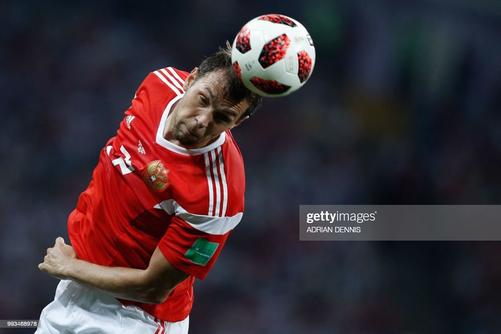 TOPSHOT - Russia's forward Artem Dzyuba heads the ball during the Russia 2018 World Cup quarter-final football match between Russia and Croatia at the Fisht Stadium in Sochi on July 7, 2018. (Photo by Adrian DENNIS / AFP) / RESTRICTED