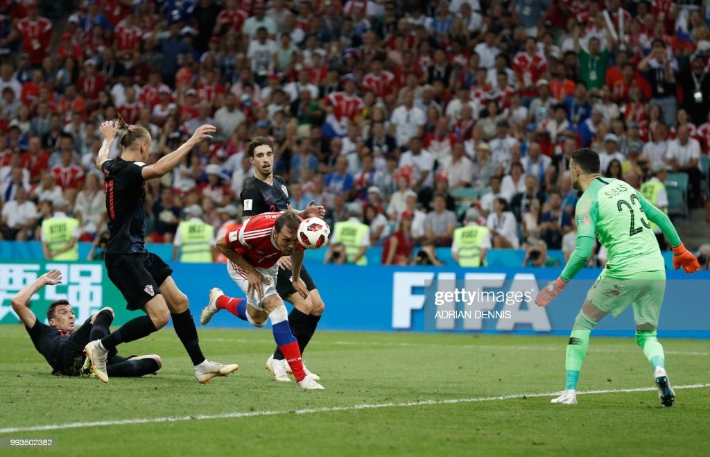 TOPSHOT - Russia's forward Artem Dzyuba (C) heads the ball during the Russia 2018 World Cup quarter-final football match between Russia and Croatia at the Fisht Stadium in Sochi on July 7, 2018. (Photo by Adrian DENNIS / AFP) / RESTRICTED