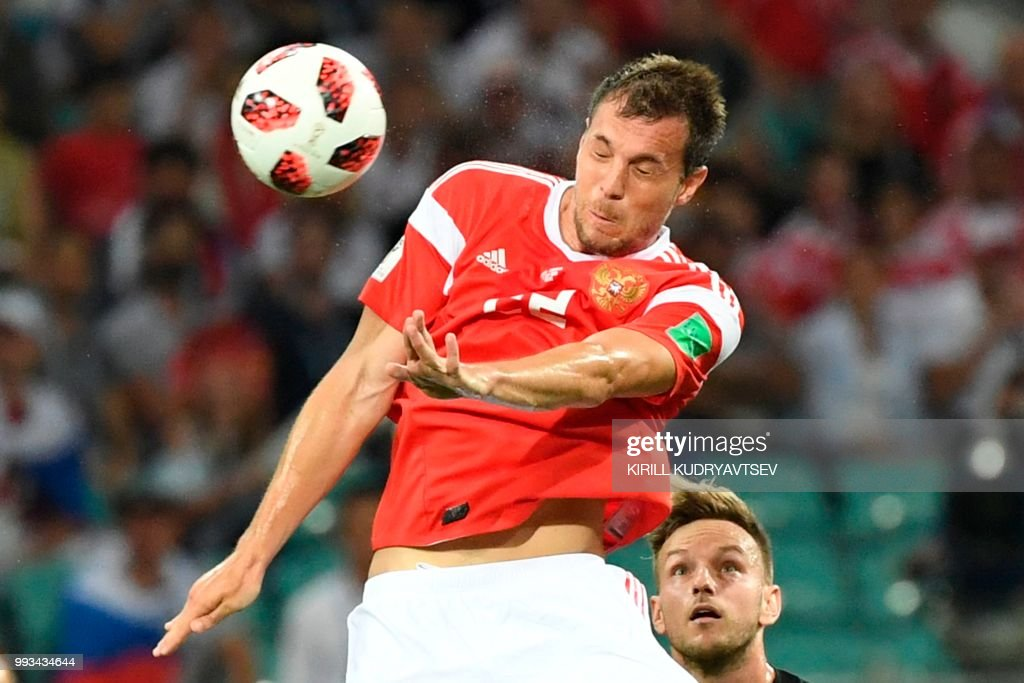 TOPSHOT - Russia's forward Artem Dzyuba heads the ball next to Croatia's midfielder Ivan Rakitic during the Russia 2018 World Cup quarter-final football match between Russia and Croatia at the Fisht Stadium in Sochi on July 7, 2018. (Photo by Kirill KUDRYAVTSEV / AFP) / RESTRICTED