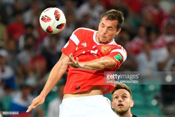 Russia's forward Artem Dzyuba heads the ball next to Croatia's midfielder Ivan Rakitic during the Russia 2018 World Cup quarter-final football match...