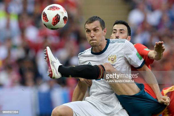 TOPSHOT Russia's forward Artem Dzyuba vies with Spain's midfielder Sergio Busquets during the Russia 2018 World Cup round of 16 football match...