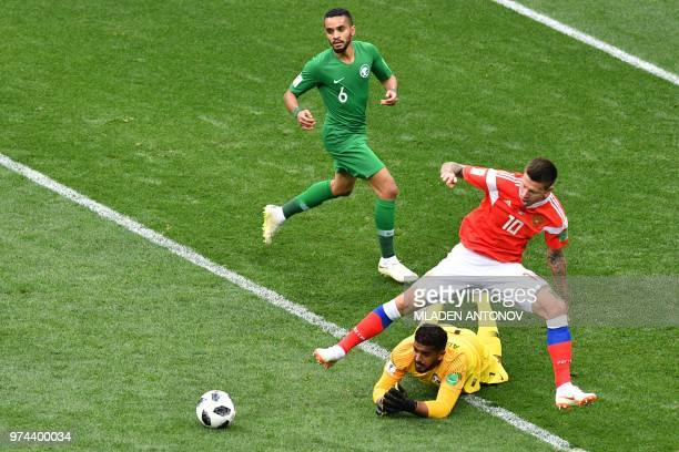 Russia's forward Fedor Smolov and Saudi Arabia's goalkeeper Abdullah AlMayouf compete for the ball during the Russia 2018 World Cup Group A football...