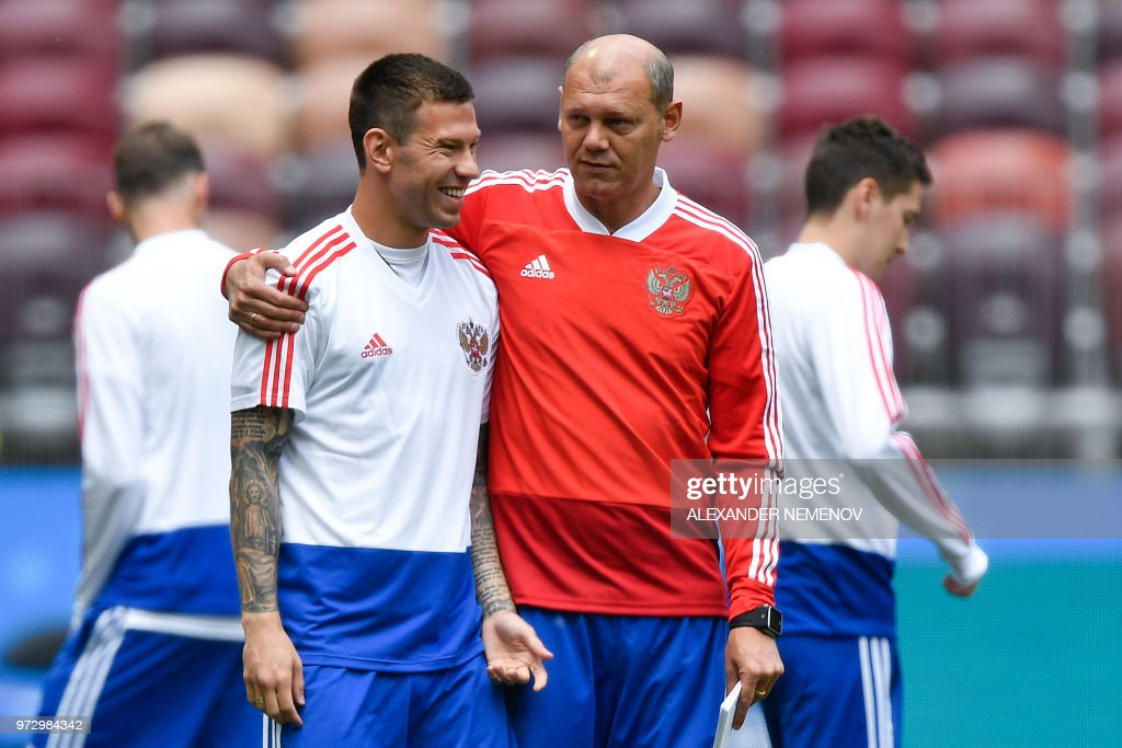 Russia's forward Fedor Smolov chats with assistant coach Miroslav Romaschenko (R) during a training session at the Luzhniki Stadium in Moscow on June 13, 2018 ahead of the Russia 2018 World Cup opening football match between Russia and Saudi Arabia.