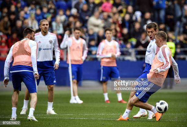 Russia's forward Fyodor Smolov and Russia's defender Andrey Semyonov vie for the ball during a training session at Moscow's VEB Arena stadium on June...
