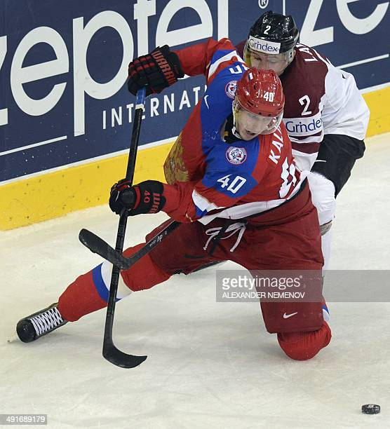 Russia's forward Sergei Kalinin vies for the puck with Latvia's defender Rodrigo Lavins during a IIHF International Ice Hockey World Championship...