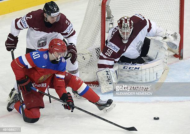 Russia's forward Sergei Kalinin vies for the puck with Latvia's defender Rodrigo Lavins and Latvia's goalie Kristers Gudlevskis during a IIHF...