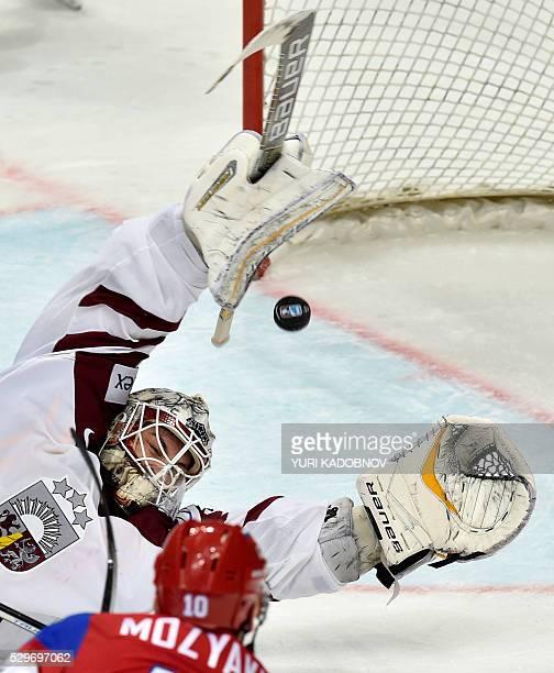 Russia's forward Sergei Mozyakin attacks Latvia's goalie Elvis Merzlikins during the group A preliminary round game Latvia vs Russia at the 2016 IIHF...
