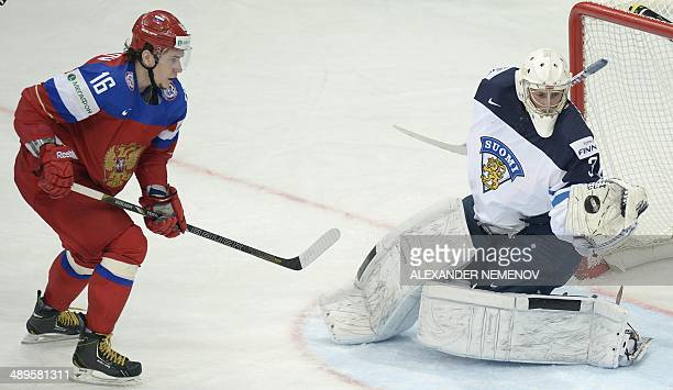 Russia's forward Sergei Plotnikov attacks Finland's goalie Mikko Koskinen during a preliminary round group B game Russia vs Finland of the IIHF...