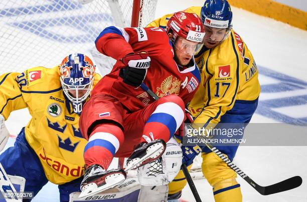 TOPSHOT Russia's forward Sergey Andronov fights for the puck with Sweden's forward Par Lindholm in front of Sweden's goaltender Viktor Fasth during...