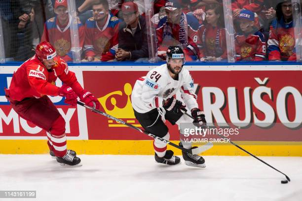 Russia's forward Yevgeni Malkin and Austria's defender Steven Strong vie for the puck during the IIHF Men's Ice Hockey World Championships Group B...