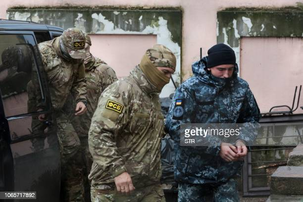 A Russia's FSB security service officer escorts a detained Ukrainian sailor to a courthouse in Simferopol Crimea on November 27 2018 A court in...