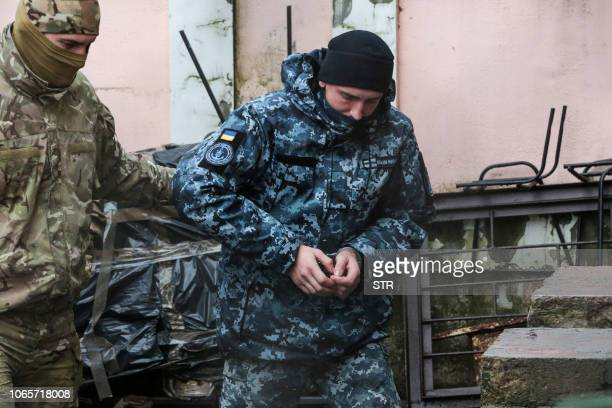 Russia's FSB security service officer escorts a detained Ukrainian sailor to a courthouse in Simferopol Crimea on November 27 2018 A court in...