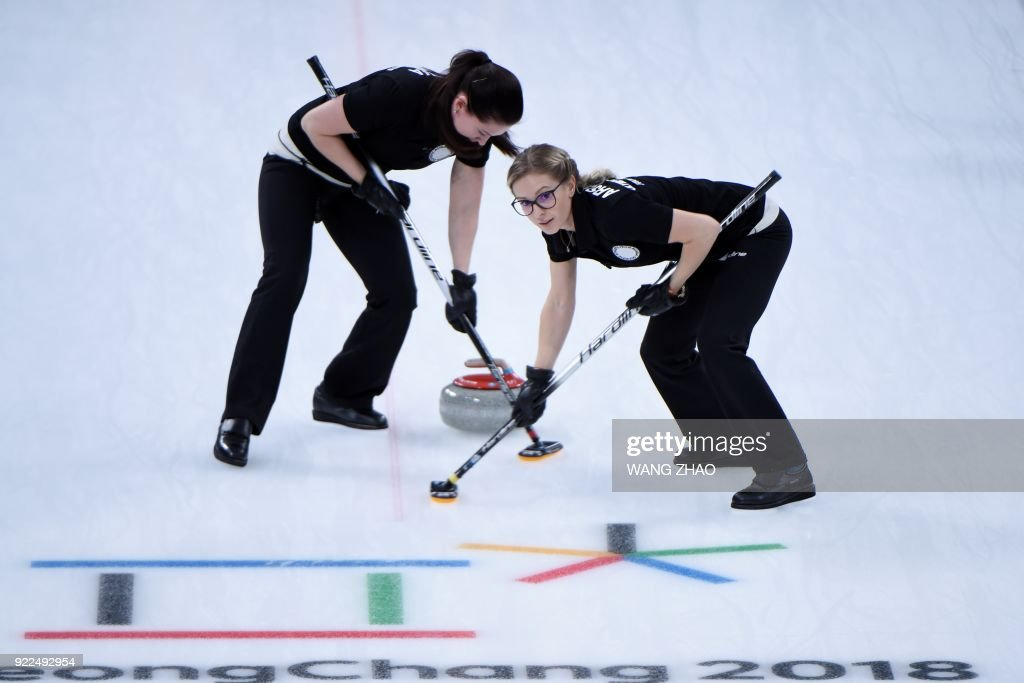 Russia's Galina Arsenkina (R) brushes in front of the stone with her teammate during the curling women's round robin session between the Olympic Athletes from Russia and Canada during the Pyeongchang 2018 Winter Olympic Games at the Gangneung Curling Centre in Gangneung on February 21, 2018. / AFP PHOTO / WANG Zhao