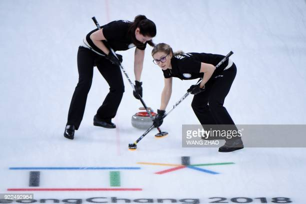 Russia's Galina Arsenkina brushes in front of the stone with her teammate during the curling women's round robin session between the Olympic Athletes...