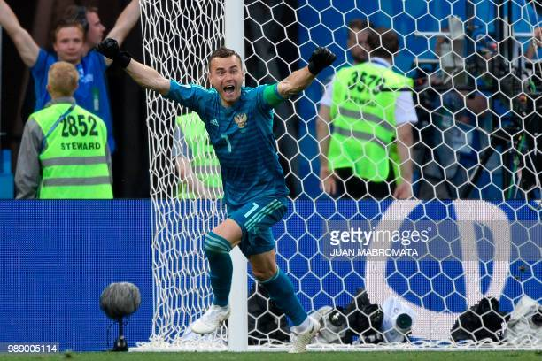 TOPSHOT Russia's goalkeeper Igor Akinfeev celebrates after stopping a shot by Spain's forward Iago Aspas during the penalty shootout of the Russia...