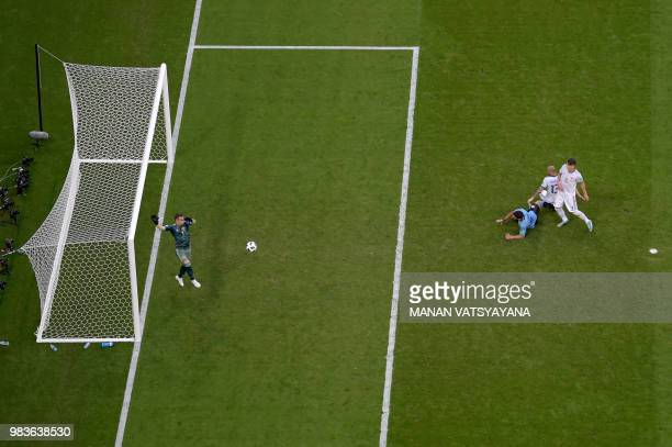 Russia's goalkeeper Igor Akinfeev covers the ball during the Russia 2018 World Cup Group A football match between Uruguay and Russia at the Samara...