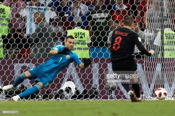 TOPSHOT Russia's goalkeeper Igor Akinfeev dives to save a penalty from Croatia's midfielder Mateo Kovacic during the Russia 2018 World Cup...