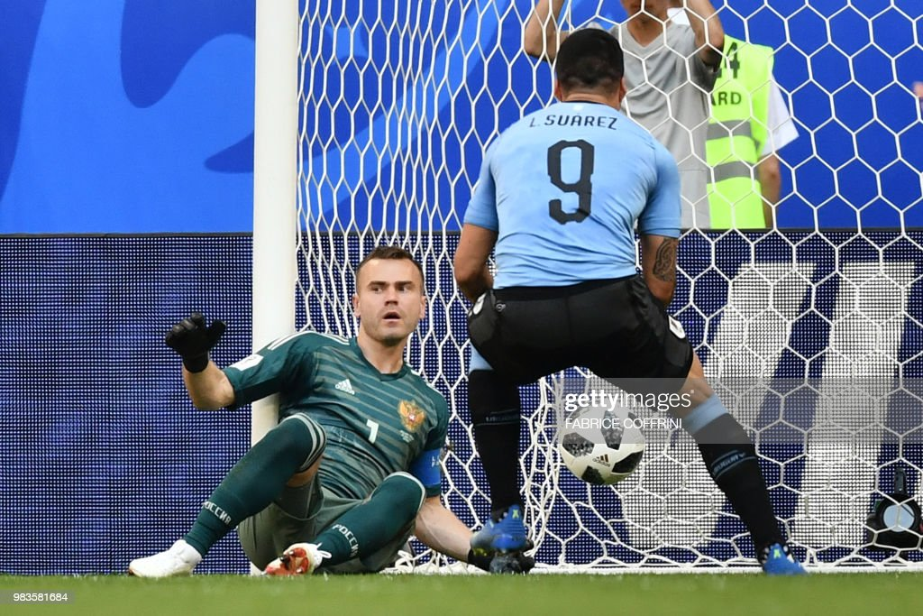 TOPSHOT - Russia's goalkeeper Igor Akinfeev (L) reacts as Uruguay's forward Luis Suarez picks up the ball after Uruguay scored a second goal during the Russia 2018 World Cup Group A football match between Uruguay and Russia at the Samara Arena in Samara on June 25, 2018. (Photo by Fabrice COFFRINI / AFP) / RESTRICTED