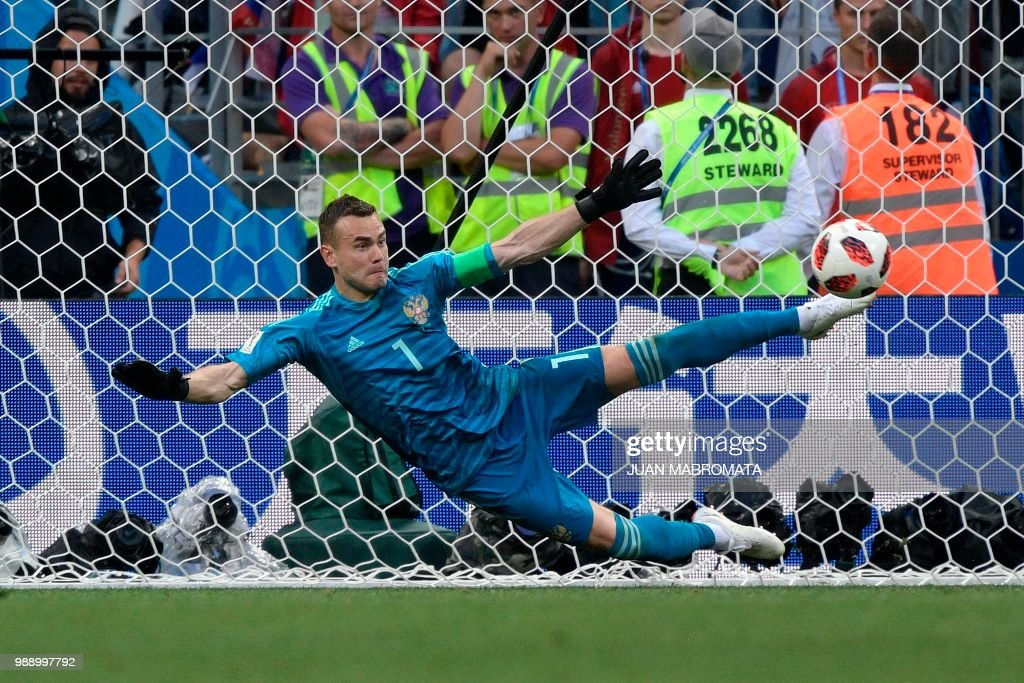 TOPSHOT - Russia's goalkeeper Igor Akinfeev stops a shot by Spain's forward Iago Aspas during the penalty shootout of the Russia 2018 World Cup round of 16 football match between Spain and Russia at the Luzhniki Stadium in Moscow on July 1, 2018. (Photo by Juan Mabromata / AFP) / RESTRICTED