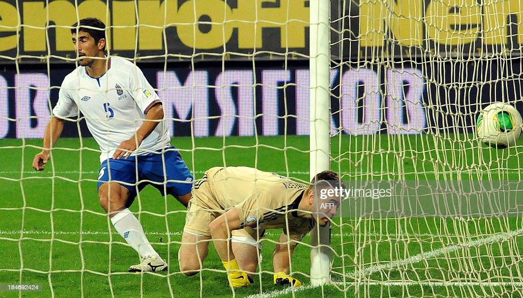 Russia's goalkeeper Igor Akinfeyev (R) loses a ball as Azeri Elnur Allahverdiyev (L) reacts during their FIFA World Cup 2014 qualifying football match between Azerbaijan and Russia in Baku on October 15, 2013.