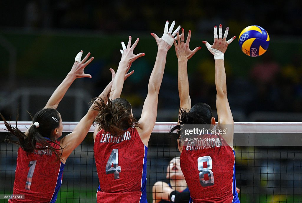 TOPSHOT - Russia's Iana Shcherban (L), Irina Zarayazhko (C) and Nataliya Goncharova try to block the ball during the women's qualifying volleyball match between Russia and South Korea at the Maracanazinho stadium in Rio de Janeiro on August 8, 2016, during the 2016 Rio Olympics. / AFP / Johannes EISELE