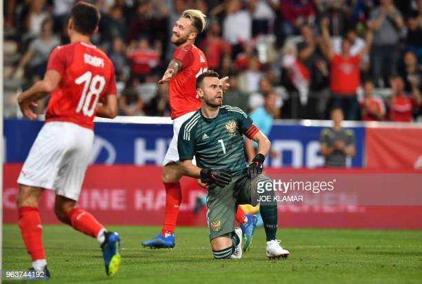 Russia's Igor Akinfeev looks on as Austria's Alessandro Schoepf and Austria's Peter Zulj celebrate scoring the 10 goal during their international...
