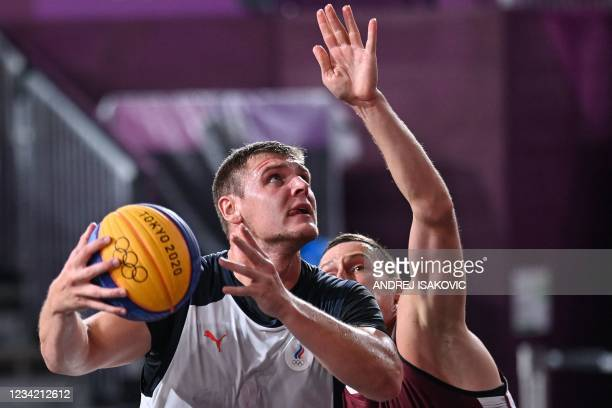 Russia's Ilia Karpenkov fights for the ball with Latvia's Agnis Cavars during the men's first round 3x3 basketball match between Russia and Latvia at...