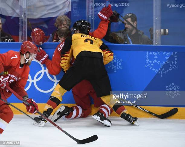TOPSHOT Russia's Ilya Kablukov is checked by Germany's Daryl Boyle in the men's gold medal ice hockey match between the Olympic Athletes from Russia...