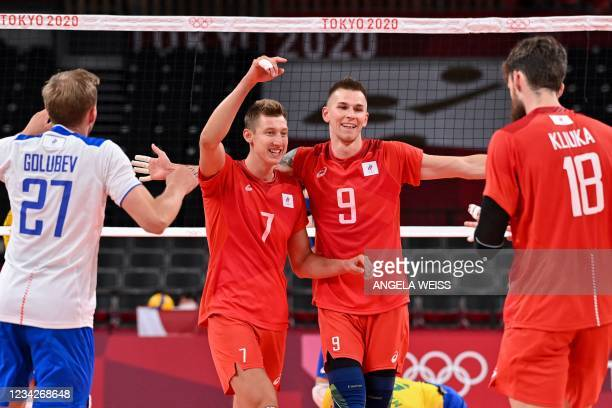 Russia's Ivan Iakovlev and Dmitry Volkov react after a point in the men's preliminary round pool B volleyball match between Brazil and Russia during...
