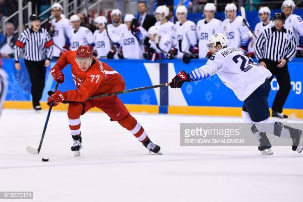 TOPSHOT Russia's Kirill Kaprizov and US Mark Arcobello vie for the puck in the men's ice hockey preliminary round group B game between the Olympic...