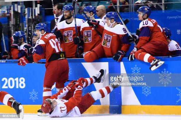 TOPSHOT Russia's Kirill Kaprizov falls on the ice in front of the Czech Republic bench in the men's semifinal ice hockey match between the Czech...