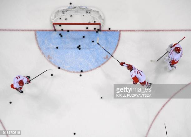 Russia's Kirill Kaprizov pushes a puck as he warms up before the men's preliminary round ice hockey match between Slovakia and Olympic Athletes from...