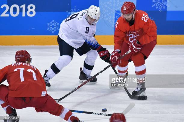 Russia's Kirill Kaprizov US Brian O'Neill and Russia's Vyacheslav Voinov vie for the puck in the men's ice hockey preliminary round group B game...
