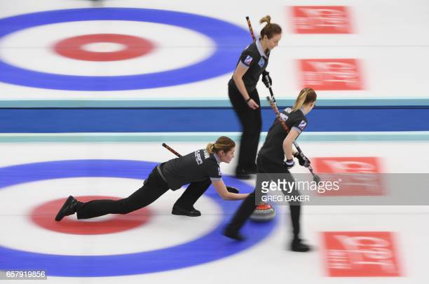 Russia's Margarita Fomina releases the stone as teammates Alexandra Raeva and Alina Kovaleva look on during the gold medal match against Canada at...