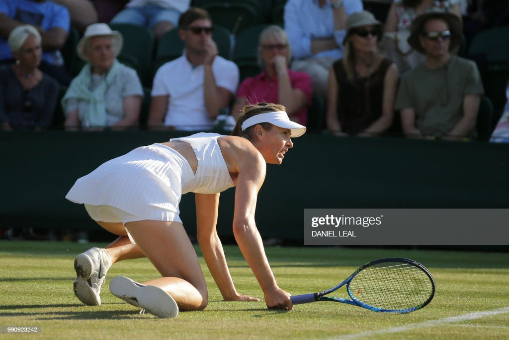 TOPSHOT - Russia's Maria Sharapova falls while playing Russia's Vitalia Diatchenko during their women's singles first round match on the second day of the 2018 Wimbledon Championships at The All England Lawn Tennis Club in Wimbledon, southwest London, on July 3, 2018. (Photo by Daniel LEAL-OLIVAS / AFP) / RESTRICTED