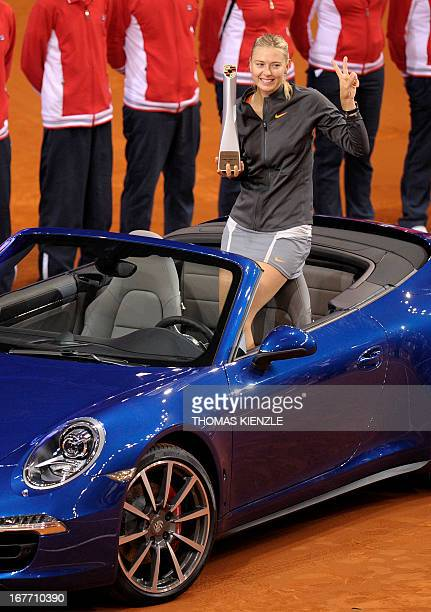 Russia's Maria Sharapova holds her trophy and gestures in the winner's prize a Porsche 911 Carrera 4 S Cabriolet after defeating China's Li Na in the...