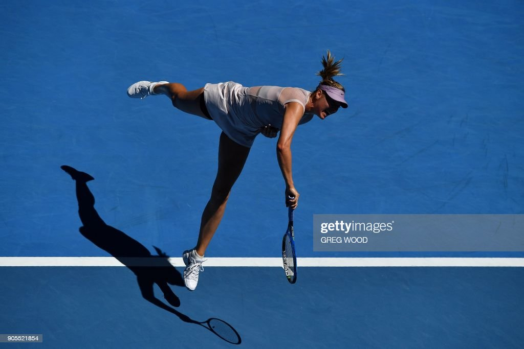 TOPSHOT - Russia's Maria Sharapova serves against Germany's Tatjana Maria during their women's singles first round match on day two of the Australian Open tennis tournament in Melbourne on January 16, 2018. / AFP PHOTO / Greg Wood / -- IMAGE