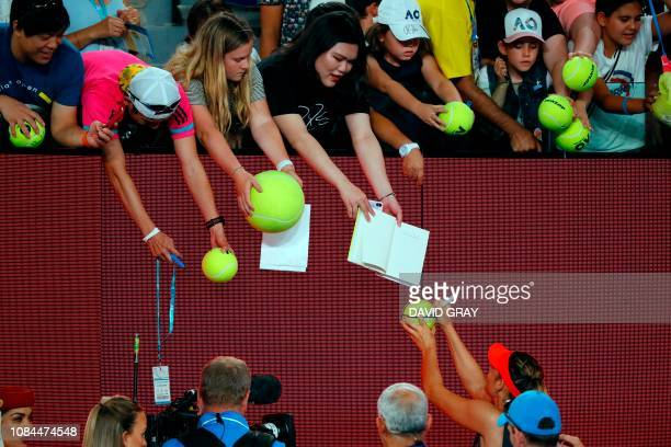 Russia's Maria Sharapova signs autograph to her supporters after the women's singles match against Denmark's Caroline Wozniacki on day five of the...