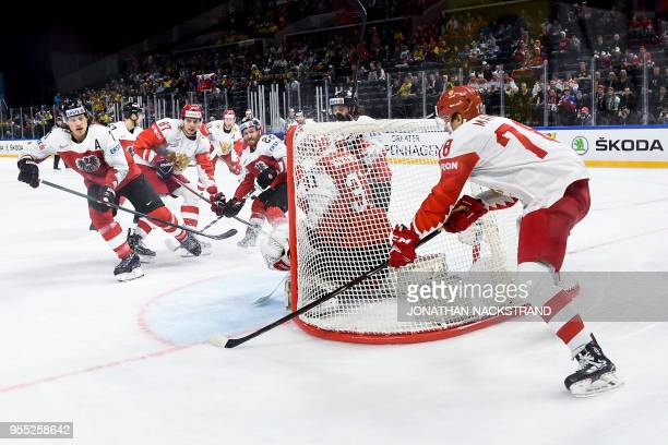 Russia's Maxim Mamin strikes behind Austria's goalie David Madlener during the group A match Austria vs Russia of the 2018 IIHF Ice Hockey World...